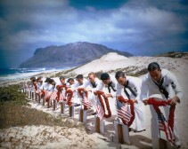 Navy Men Placing Hawaiian Leis on Gravesite of War Heroes